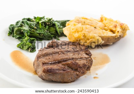 "Steak beautifully grilled with deep grill marks on plate with its own juice (au jus) and served with ""Twice-Baked-Potato"" and sauteed spinach.  Selective focus and shallow depth of field. - stock photo"