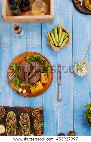 Steak grilled with stuffed zucchini, vegetables and sauce on a wooden table, top view. Outdoors Food Concept. Food background - stock photo