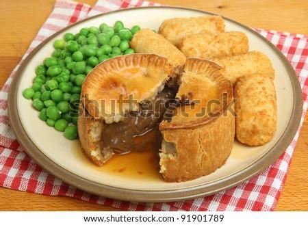 Steak pie with croquette potatoes, peas and gravy. - stock photo