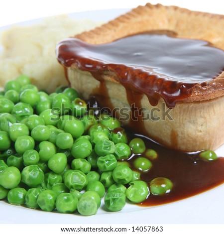 Steak pie with mashed potato, peas and gravy - stock photo