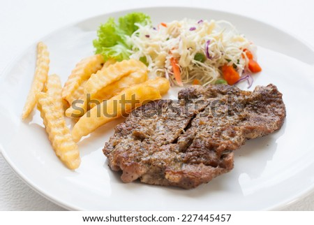 steak served with crisp golden French fries and fresh green herb salad - stock photo