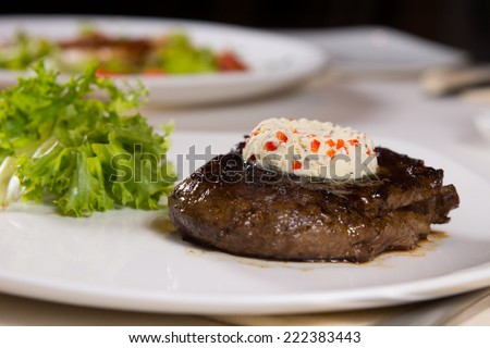 Steak Topped with Herbed Butter on Plate with Garnish on Table - stock photo