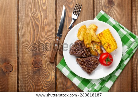Steak with grilled potato, corn, salad and tomato over wooden table. Top view with copy space  - stock photo