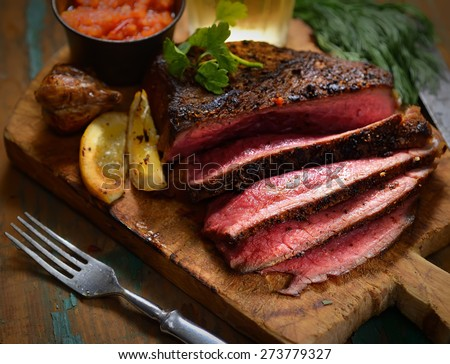 Steak with herbs and beer on a wooden background - stock photo