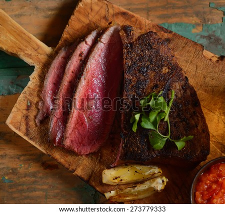 steak with herbs on a wooden background - stock photo