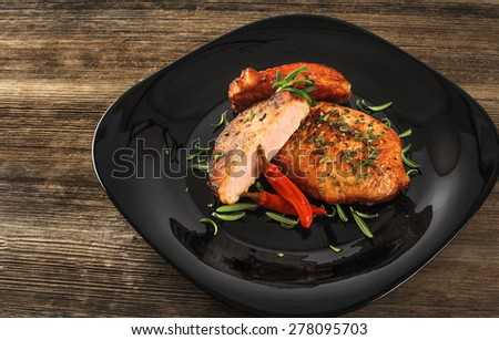 Steak with rosemary and chili pepper on a plate - stock photo