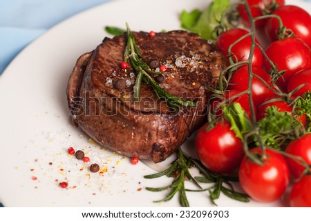 steak with rosemary and pepper and coarse salt on a plate - stock photo