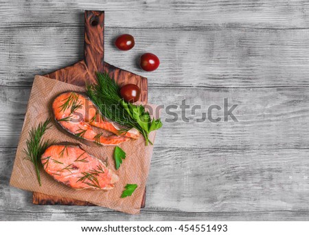 Steaks salmon fish on cutting board, parsley, dill on paper for fish steaks, light wooden background surface, top view, empty place for text, recipe - stock photo