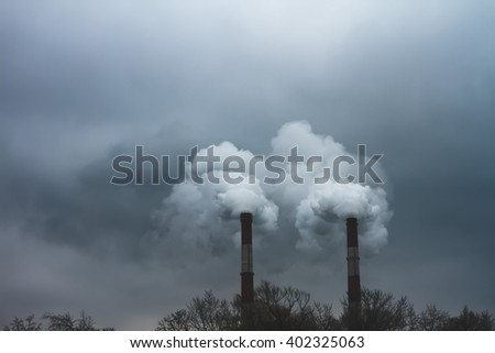 Steam and smoke is formed from boiler and turbine house at sunset. This boiler is a part of the thermal plant power in the industrial zone. The theme of global warming and environmental pollution. - stock photo