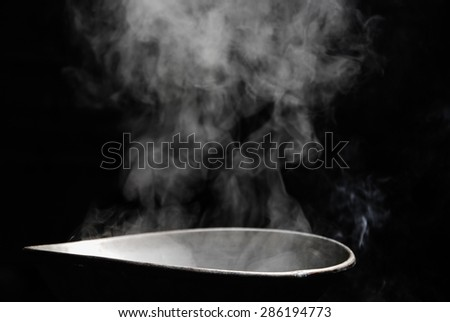 Steam and smoke over cooking pot - stock photo