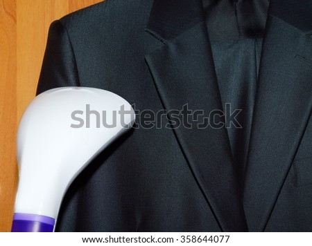 steam cleaning a suit in the laundry - stock photo