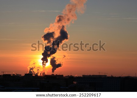 Steam from one of the city's heating power plants is seen at sunset in Bucharest, Romania in an extremely cold winter day. - stock photo