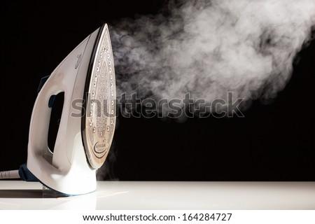 steam generator iron on black background - stock photo
