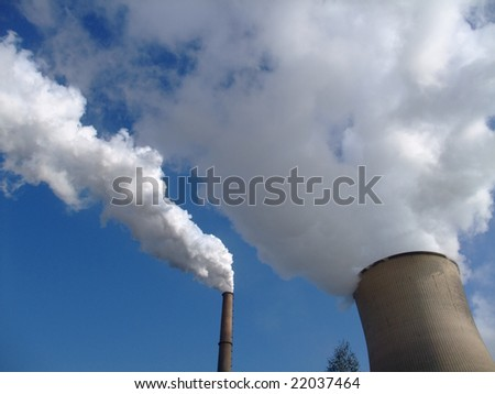 Steam geting out of a cooling tower of a coal power plant into blue sky - stock photo