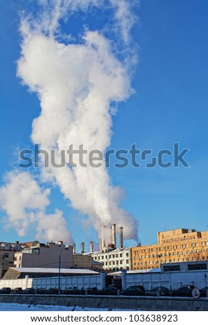 Steam goes from thermal power plant pipes in the large city. - stock photo