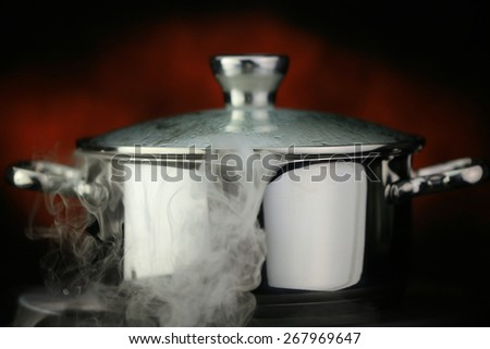 steam over cooking pot on a red background - stock photo