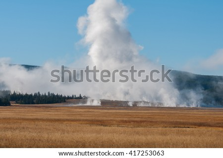 Steam rising near a meadow in Yellowstone National Park Wyoming. - stock photo