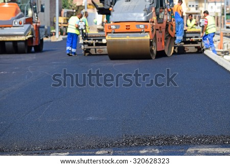 Steam rollers at the road construction in the city - stock photo