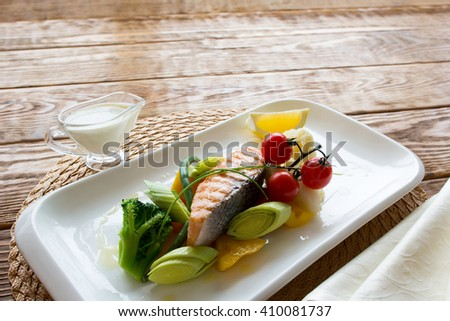Steam salmon with a side dish of fresh vegetables on a white square plate. Top view on lenten meal.  - stock photo