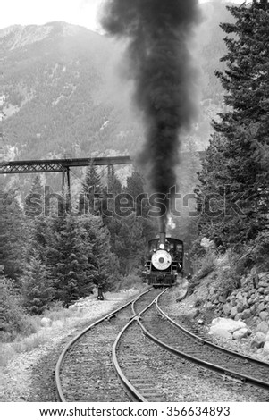 Steam train is coming up. Black and white photography. - stock photo
