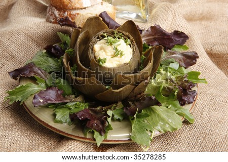 Steamed Artichoke stuffed with Hollandaise sauce - stock photo