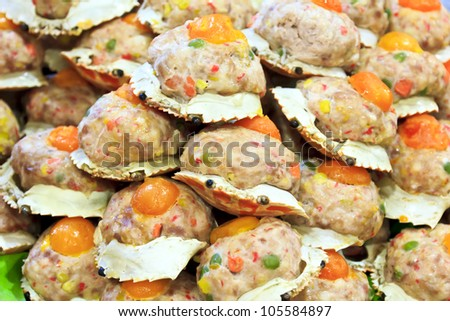 Steamed crab meat, pork and various ingredients stuffed shell topped with salted egg yolk. - stock photo