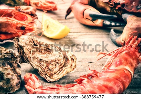Steamed crab, shrimps and fresh oysters on wooden background. Sea food dinner concept - stock photo