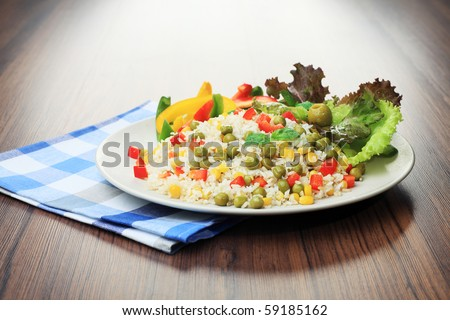 Steamed long rice with green peas, corn and pepper on a table. - stock photo