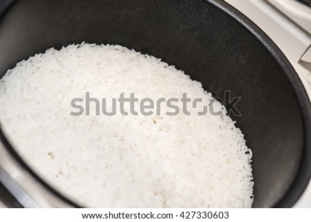 steamed rice in the  inner pot of electric rice cooker - stock photo