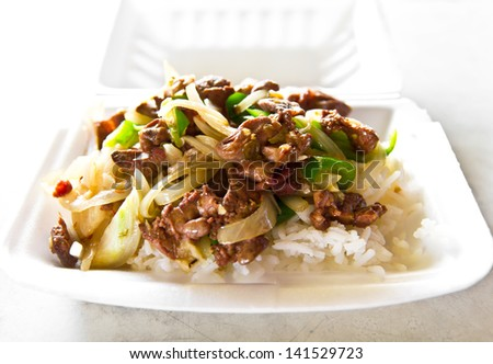 Steamed rice topped with a fried chicken with onion and bell pepper in a foam box. - stock photo