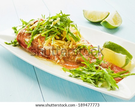 Steamed sea bass with rucola and ginger in olive and linseed oil. Shallow dof.  - stock photo