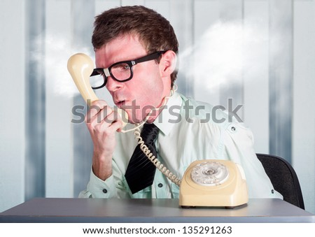 Steaming angry nerd businessman holding retro phone cord around big red head while shouting out demands to incompetent and unskilled workers in a staff management conceptual - stock photo