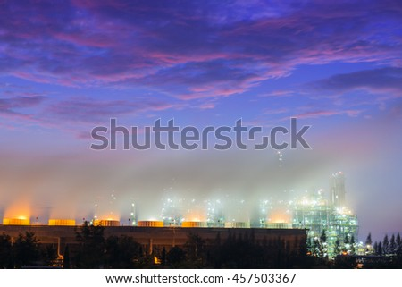 Steaming cooling tower of oil refinery plant, Twilight shot. - stock photo