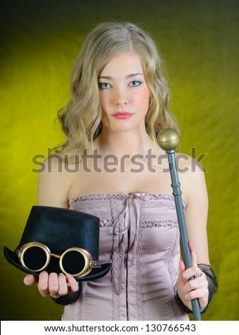 Steampunk female with a cane, top hat and goggles. - stock photo