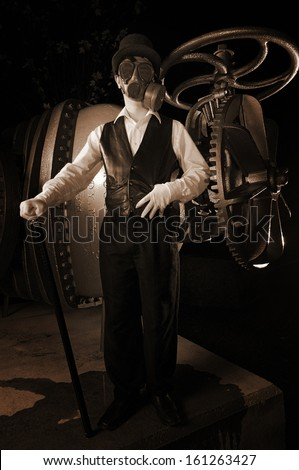 Steampunk figure in top hat and gas mask stands near huge gears and valves - stock photo