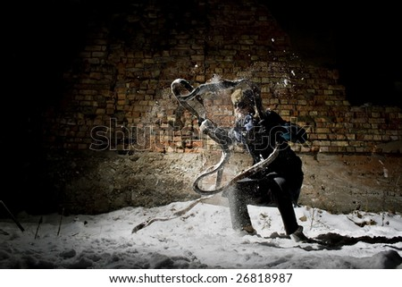 steampunker near the wall in snow - stock photo