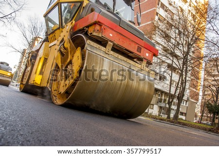 Steamroller asphalting city roads  - stock photo