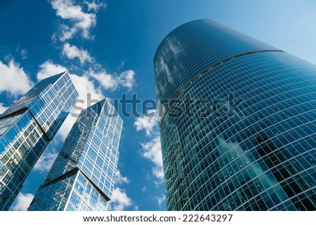 Steel and glass corporate buildings reflect the sky and clouds, Moscow - stock photo