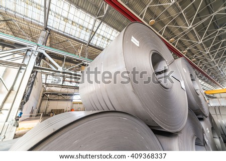 Steel coils stacked in a warehouse. - stock photo