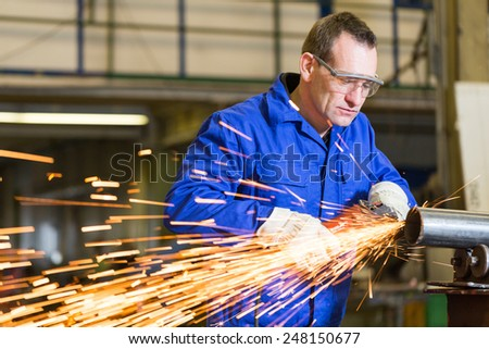 Steel construction worker grinding metal with an angle grinder - stock photo