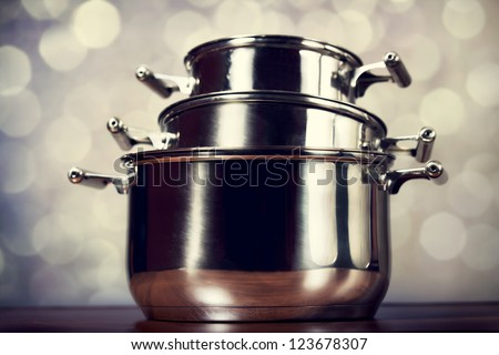 Steel cooking pots with bokeh at background - stock photo