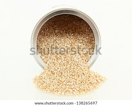 Steel Cut Oatmeal Spilling Out Of A Container - stock photo