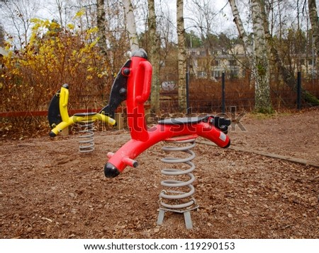 Steel horses, standing alone in a children's playground - stock photo