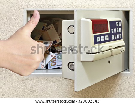 Steel safe with money and female hand with a thumb up showing a success. Concept of a Reliable protection and security  - stock photo