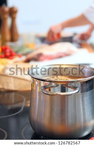 Steel saucepan with soup at the kitchen - stock photo