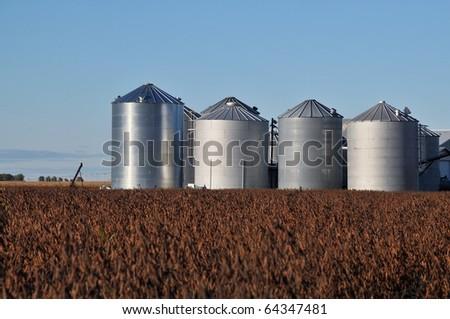 Steel silos in a grassy field in rural - stock photo