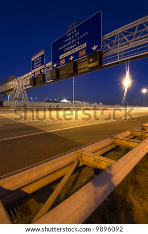Steel structures, supporting traffic signs and direction information systems above a motorway at night - stock photo