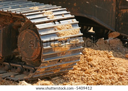 Steel tracks of a front end loader rolling through fresh dirt - stock photo