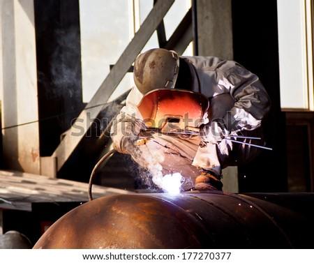 steel welding worker in fabrication workshop  - stock photo