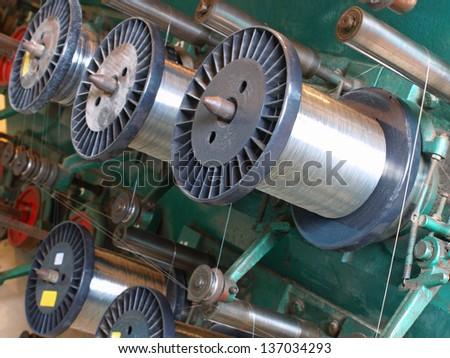 Steel wire spools.Braiding machine.Flexible metal hose production line. - stock photo